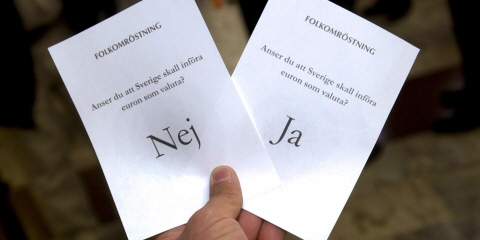 A hand holding two ballot papers from the referendum on the euro. One of them stays No and the other Yes.