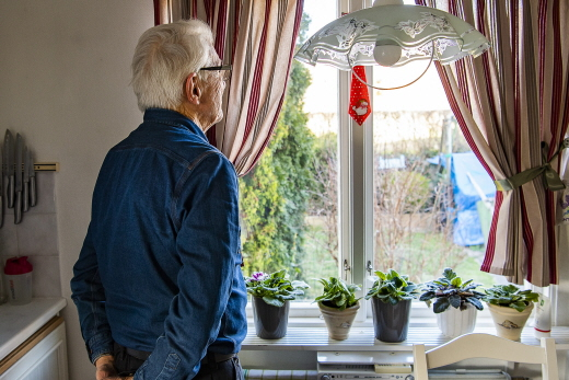 Elderly man looking out a window in his home.