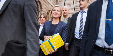 Magdalena Andersson walking with the Spring Fiscal Policy Bill in her hand. She is surrounded by guards and journalists.