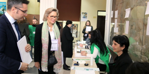 Members of the Riksdag observing an election. One of the members, Margareta Cederfelt (Mod), stands in front of a table at a polling station in Georgia.