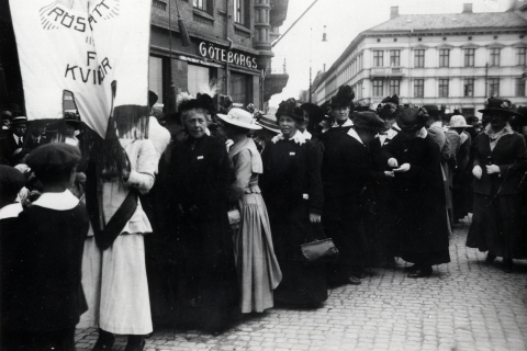 A black-and-white photo of elegantly dressed women in a demonstration. A banner bears the words